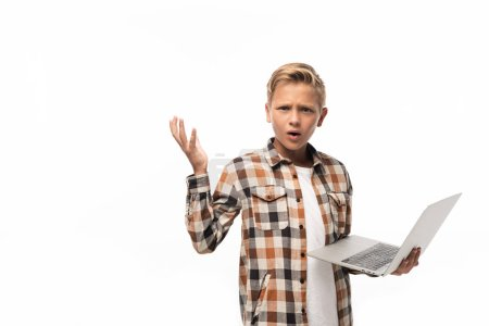 Photo for Discouraged boy holding laptop, looking at camera and showing shrug gesture isolated on white - Royalty Free Image