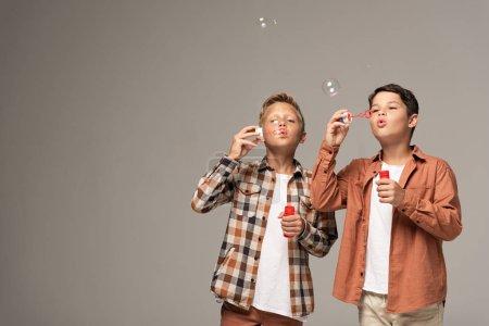 Photo pour Deux mignons garçons soufflant des bulles de savon isolé sur gris - image libre de droit