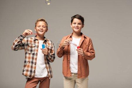 Photo pour Deux frères joyeux tenant des bouteilles avec des bulles de savon et souriant à la caméra isolée sur gris - image libre de droit