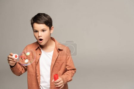 Foto de Muchacho sorprendido mirando la burbuja de jabón aislada en gris - Imagen libre de derechos