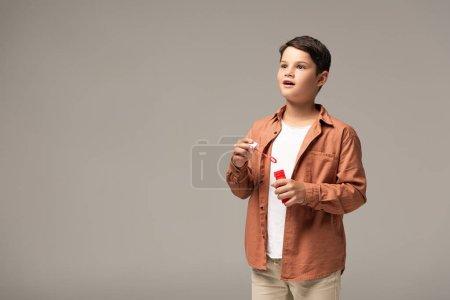 Photo pour Garçon étonné tenant bouteille avec bulles de savon et regardant loin isolé sur gris - image libre de droit