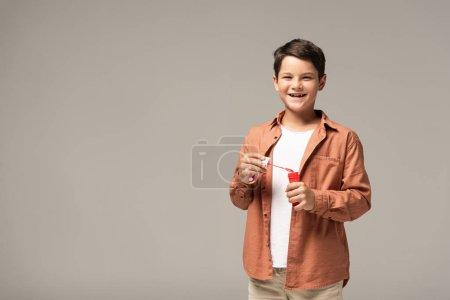 Photo pour Garçon gai tenant une bouteille avec des bulles de savon et souriant à la caméra isolé sur gris - image libre de droit
