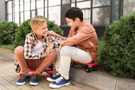 Photo pour Frères joyeux parler tout en étant assis sur le trottoir près des buissons verts - image libre de droit