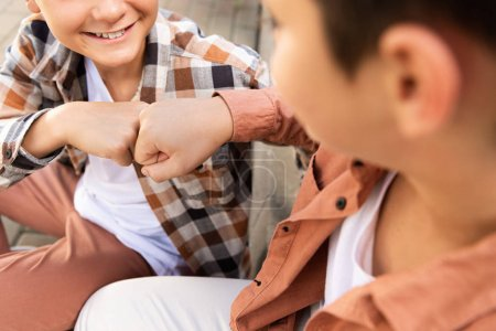 cropped view of smiling boy doing fist bump with brother