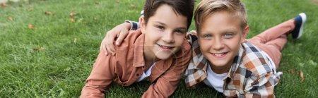 Photo pour Photo panoramique de deux heureux frères souriant à la caméra couchés sur l'herbe - image libre de droit