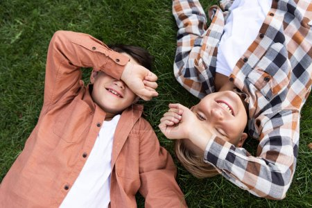 Photo for Top view of two cheerful brothers covering eyes with hands while lying on green grass - Royalty Free Image
