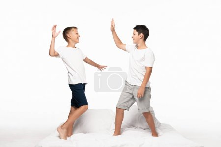 Photo for Cheerful brothers giving high five while standing on bed isolated on white - Royalty Free Image
