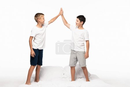 Photo for Two happy brothers standing on bed and giving high five isolated on white - Royalty Free Image