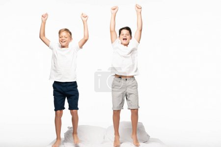 Photo for Two cheerful brothers standing on bed and showing winner gesture isolated on white - Royalty Free Image