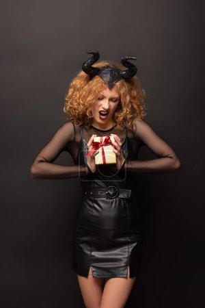 Photo pour Femme coriace effrayante en costume fantastique tenant une boîte-cadeau pour l'halloween sur noir - image libre de droit