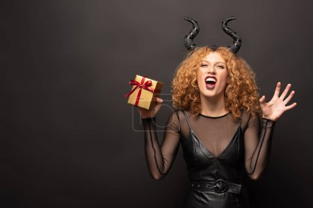 Photo for Beautiful redhead woman in halloween costume with horns holding gift box on black - Royalty Free Image
