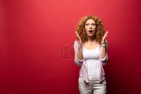 Photo pour Belle rousse choquée femme geste isolé sur rouge - image libre de droit