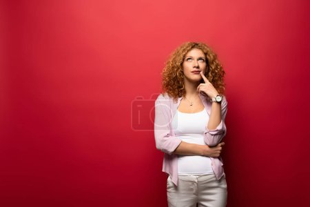 Photo for Beautiful thoughtful redhead woman gesturing isolated on red - Royalty Free Image