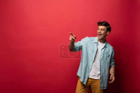 handsome laughing man in casual clothes pointing isolated on red