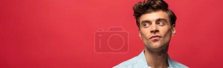 Photo pour Portrait d'un bel homme pensif en tenue décontractée isolé en rouge - image libre de droit