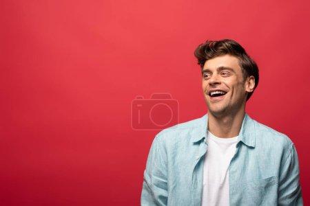 Photo pour Portrait d'un bel homme riant en tenue décontractée isolé en rouge - image libre de droit