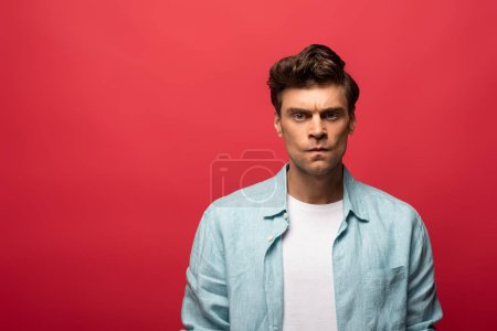 Photo for Portrait of handsome angry man in casual clothes isolated on red - Royalty Free Image