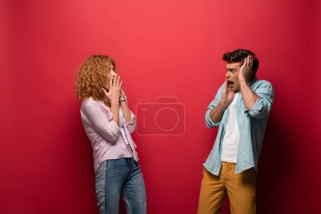 beautiful scared couple looking at each other, isolated on red