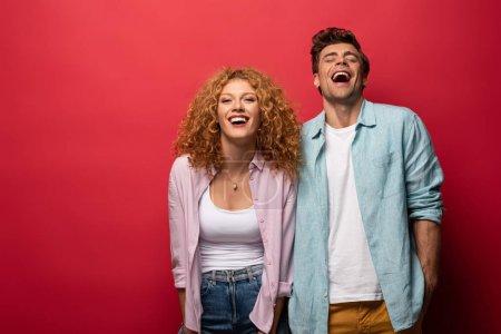 Photo pour Beau couple heureux en tenue décontractée riant isolé sur rouge - image libre de droit