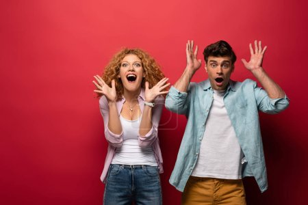 Photo for Excited woman and shocked man gesturing in casual clothes isolated on red - Royalty Free Image