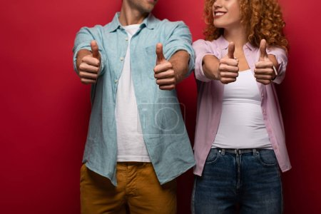 cropped view of smiling couple showing thumbs up, isolated on red