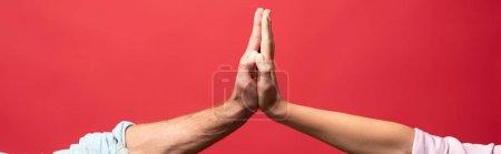 Photo pour Vue partielle du jeune couple donnant haut cinq, isolé sur rouge - image libre de droit