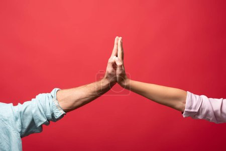Photo for Partial view of couple giving high five, isolated on red - Royalty Free Image