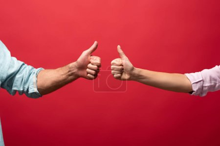 partial view of couple showing thumbs up, isolated on red