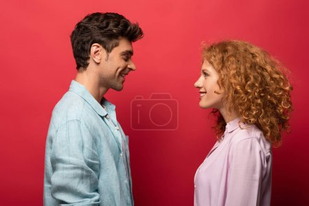 Photo pour Beau couple heureux en vêtements décontractés se regardant isolé sur rouge - image libre de droit