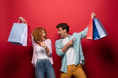 Photo for Beautiful surprised couple pointing at shopping bags, isolated on red - Royalty Free Image