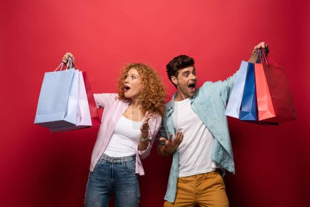 shocked couple looking at shopping bags, isolated on red
