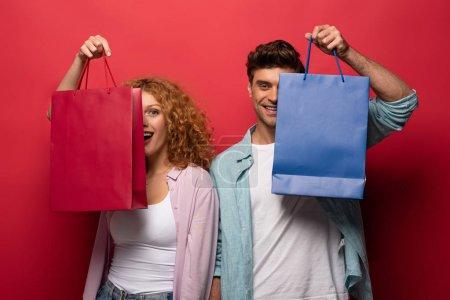 Photo pour Beau couple souriant tenant des sacs à provisions, isolé sur rouge - image libre de droit