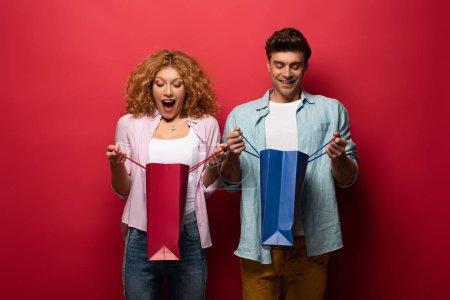 Photo pour Couple excité regardant dans des sacs à provisions, isolé sur rouge - image libre de droit