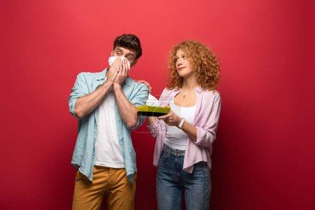 Photo pour Femme et homme malade avec nez qui coule tenant des serviettes en papier, sur rouge - image libre de droit