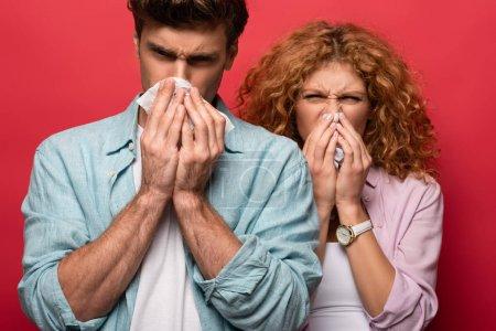Photo pour Couple malade avec nez qui coule tenant des serviettes en papier, isolé sur rouge - image libre de droit