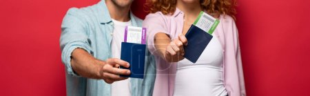 cropped view of couple showing passports with air tickets, isolated on red