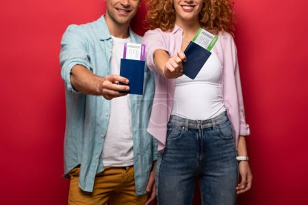 Photo for Cropped view of smiling travelers showing passports with air tickets, isolated on red - Royalty Free Image