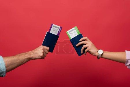 Ausgeschnittene Ansicht von Reisenden, die Pässe mit Flugtickets in der Hand halten, isoliert auf rot