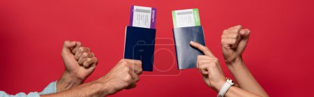 Photo for Partial view of couple holding fists and passports with air tickets, isolated on red - Royalty Free Image