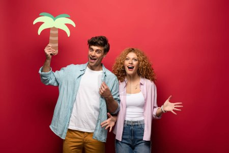 Photo for Couple of cheerful travelers holding paper palm, isolated on red - Royalty Free Image