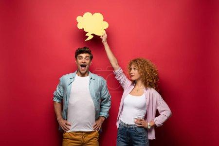 Foto de Novia sonriente que sostiene la burbuja de nubes amarillas sobre novio, sobre rojo. - Imagen libre de derechos