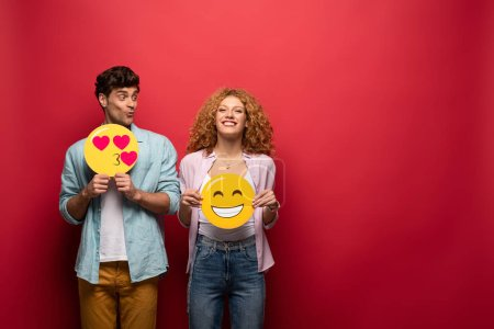 Foto de Kyiv, Ucrania - 26 de septiembre de 2019: pareja alegre con señales emoji sonrientes y sonrientes, en rojo. - Imagen libre de derechos