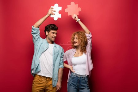 Photo for Happy couple holding puzzle pieces, isolated on red - Royalty Free Image