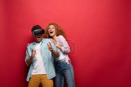 Photo for Young excited couple using virtual reality headset, isolated on red - Royalty Free Image