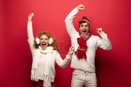 Photo for Excited couple in winter outfit screaming isolated on red - Royalty Free Image