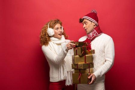 Photo pour Heureux couple en tenue d'hiver tenant cadeaux de Noël sur rouge - image libre de droit