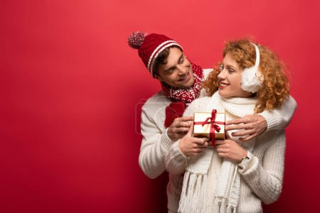 Photo pour Heureux couple en tenue d'hiver tenant cadeau de Noël isolé sur rouge - image libre de droit