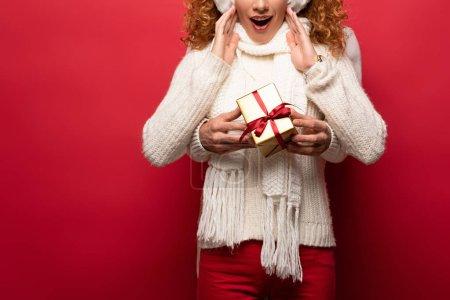 Photo pour Vue recadrée de femme surprise et l'homme en tenue d'hiver tenant cadeau de Noël isolé sur rouge - image libre de droit