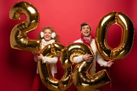 Photo for Beautiful couple in winter outfit holding new year 2020 golden balloons, on red - Royalty Free Image