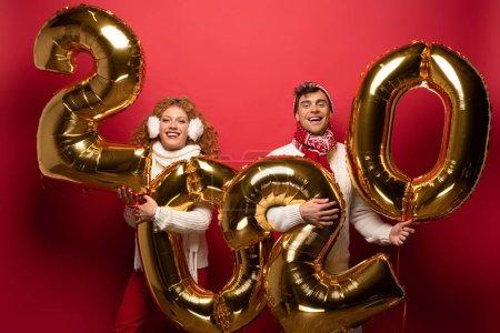 Photo pour Beau couple en tenue d'hiver tenant des ballons d'or de la nouvelle année 2020, en rouge - image libre de droit